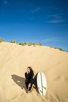Vertical shot of an attractive female sitting on a sandy hill with a surfboard on the side