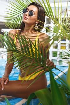 Colpo verticale di una donna attraente con una splendida abbronzatura posa vicino alla piscina al popolare.