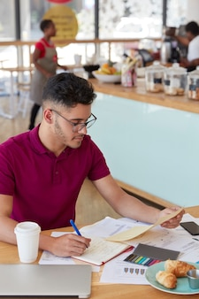 Vertical shot of attractive hipster student prepares financial project, rewrites information from document in notepad, sits at desk in cozy restaurant, wears eyewear, poses indoor. paperwork concept