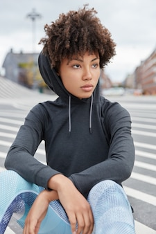 Vertical shot of attractive thoughtful african american hipster wears hoodie, sits on asphalt