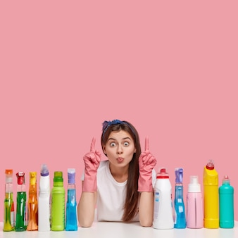 Vertical shot of attractive woman keeps lips folded, points above at blank space, shows place to wash, surrounded with bottles of various detergents, wears rubber protective gloves, headband