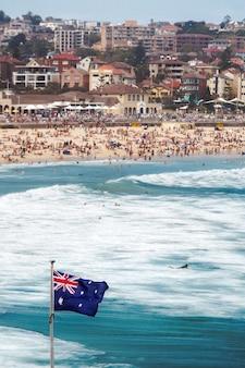 Colpo verticale della bandiera australiana al mare in un'affollata spiaggia di bondi