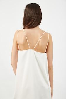 Colpo verticale della parte posteriore di una donna in un abito bianco chiaro sotto le luci in uno studio