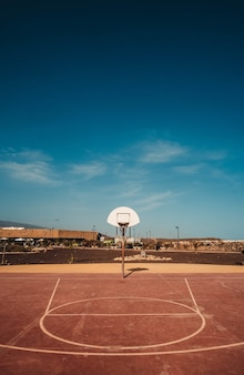 Vertical shot of a basketball court with the hoop visible under the blue sky
