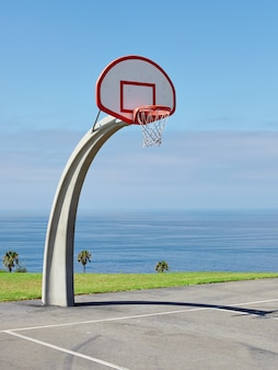 Vertical shot of a basketball hoop near the sea under the beautiful blue sky