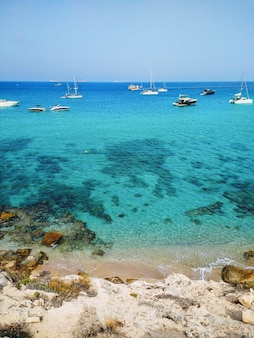 Vertical shot of the beach next to ibiza and boats in it