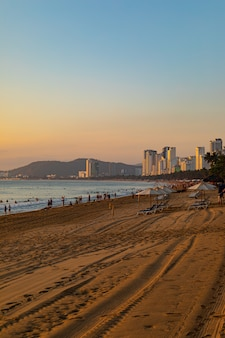 Vertical shot of a beach shore with people walking around in nha trang