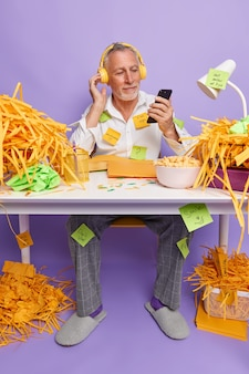 Vertical shot of bearded elderly man works in home office holds mobile phone in hand listens music via headphones dressed in domestic clothes makes list to do on sticky notes sits at table indoor