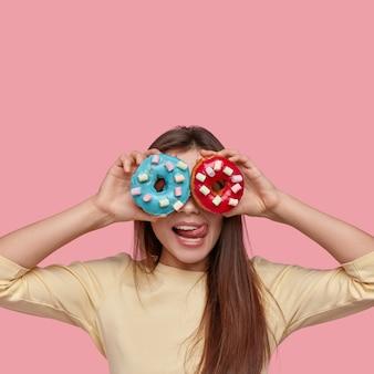 Il colpo verticale della bella signora copre gli occhi ha due ciambelle blu e rosse