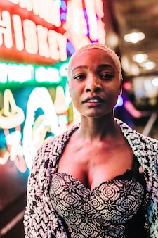 Colpo verticale di una bella donna africana in piedi vicino a luci al neon