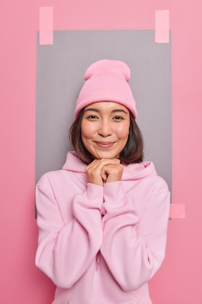 Vertical shot of beautiful asian woman with dark hair keeps hands under chin smiles gently wears hat and hoodie looks directly at camera poses against blank sheet plastered to wall