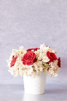 Colpo verticale di un bellissimo bouquet con rose rosse e fiori di giglio in una scatola