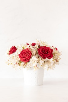 Vertical shot of a beautiful bouquet with red roses and lily flowers in a box