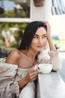 Vertical shot of beautiful brunette woman with golden tan, sitting at a cafe with a cup of coffee and looking at street.