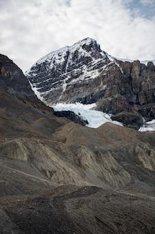 Ripresa verticale di un bellissimo paesaggio di nuvole sopra formazioni rocciose ruvide coperte di neve in campagna