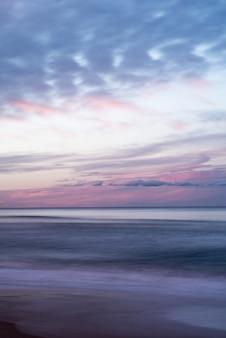 Colpo verticale del bellissimo cielo colorato sul mare durante l'alba