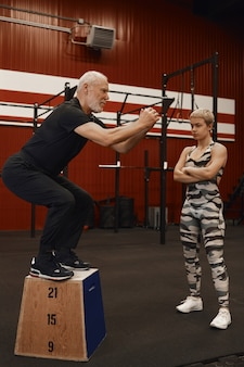 Colpo verticale di istruttore di fitness bella donna sicura di sé incrociando le braccia sul petto e guardando il suo maschio anziano facendo squat, costruendo i muscoli durante l'allenamento personale nella moderna palestra
