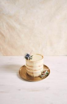 Colpo verticale di una bella e deliziosa torta con fiori e bordi dorati su sfondo bianco