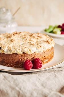 Colpo verticale di una bella e deliziosa torta di lamponi e rabarbaro con ingredienti su un tavolo