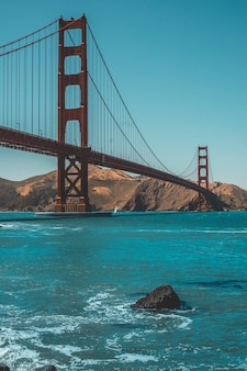 Vertical shot of the beautiful golden gate bridge and amazing clear blue sky