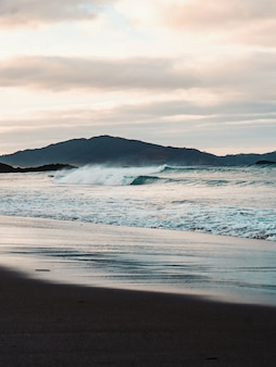 Vertical shot of the beautiful sea waves on the beach with the mountains