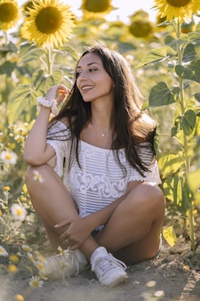 Colpo verticale di una bellissima giovane femmina caucasica in posa in un campo di girasoli