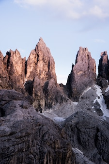 Vertical shot of big rocks on top of a mountain with a clear sky in the