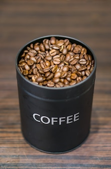 Vertical shot of a black can with coffee beans on a wooden surface