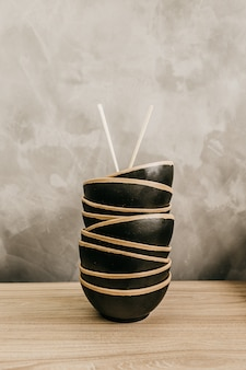 Vertical shot of black food bowls stacked on top of each other with chopsticks on top