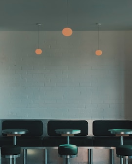 Vertical shot of black stools beside pedestal tables and benches inside a cafe