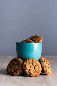 Vertical shot of a blue mug of milk and chocolate chip cookies around it