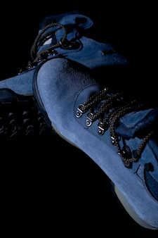 Colpo verticale di scarponi da trekking invernali blu su sfondo nero