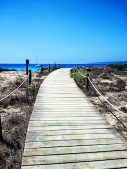 Vertical shot of the boardwalk next to a beach in formentera, spain