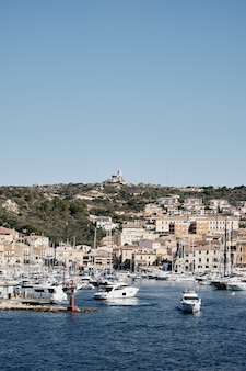 Vertical shot of boats on the water near buildings on the hill with a blue sky in the