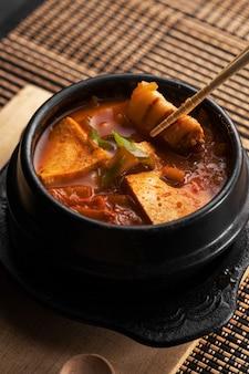 Colpo verticale di una ciotola di deliziosa zuppa di verdure e patate su un tavolo di legno