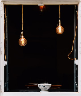 Vertical shot of a bowl on a window with pendant lights and a black
