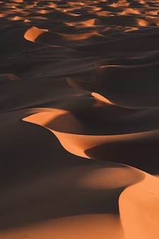 Vertical shot of the breathtaking desert hills under the sunlight captured in morocco