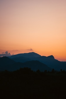 Vertical shot of a breathtaking sunset over the forest surrounded by mountains