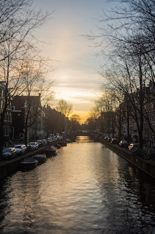 Scatto verticale di un tramonto mozzafiato sul fiume nel sud-est di amsterdam