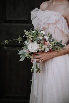 Vertical shot of a bride wearing wedding dress holding a flower bouquet