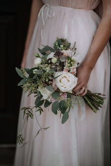 Vertical shot of a bride wearing wedding dress holding a flower bouquet