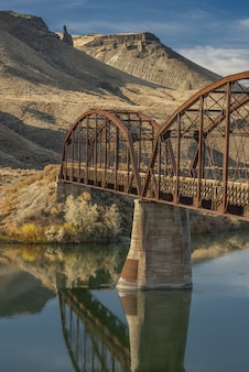 Vertical shot of a bridge over the river with mountains and a blue sky