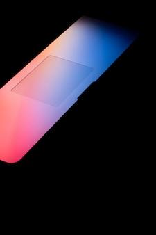 Colpo verticale di una luce colorata brillante che esce dallo schermo di un laptop nell'oscurità