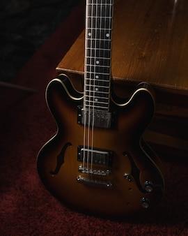 Colpo verticale di una chitarra acustica marrone sul terreno