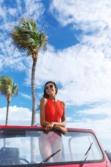 Vertical shot of brunette woman travel to the beach on a sunny day, standing in a suv car with blue sky and palm tree on background.