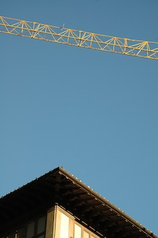 Vertical shot of a building's roof and a crane with a clear sky