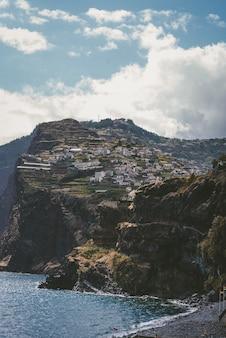 Colpo verticale di edifici sulla montagna sotto un cielo blu a funchal, madeira, portogallo.