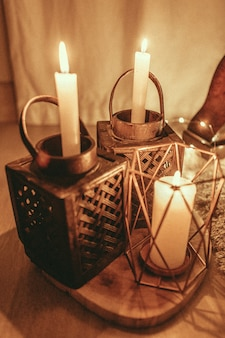 Vertical shot of burning candles with a beautiful design of candle holders