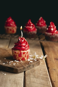 Vertical shot of a candle cupcake with red cream