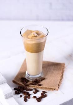 Colpo verticale di un frullato al caramello su un tovagliolo marrone circondato da chicchi di caffè